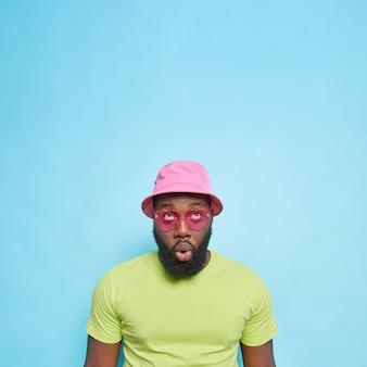 Onder de indruk verraste man met dikke baard gefocust boven houdt mond open draagt panama casaul groen t-shirt hartvormige zonnebril geïsoleerd over blauwe muur