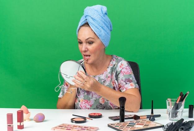 Onder de indruk volwassen blanke vrouw met gewikkeld haar in een handdoek zittend aan tafel met make-up tools die lipgloss vasthouden en kijken naar spiegel geïsoleerd op groene muur met kopieerruimte