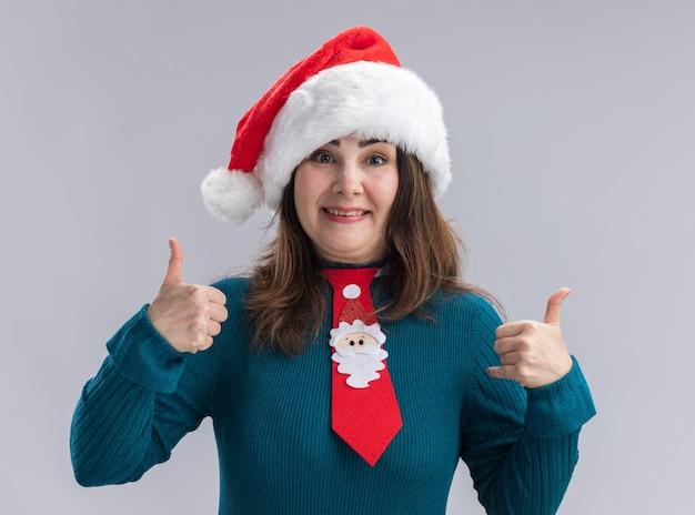 Onder de indruk volwassen blanke vrouw met kerstmuts en santa stropdas duimen omhoog geïsoleerd op een witte muur met kopie ruimte