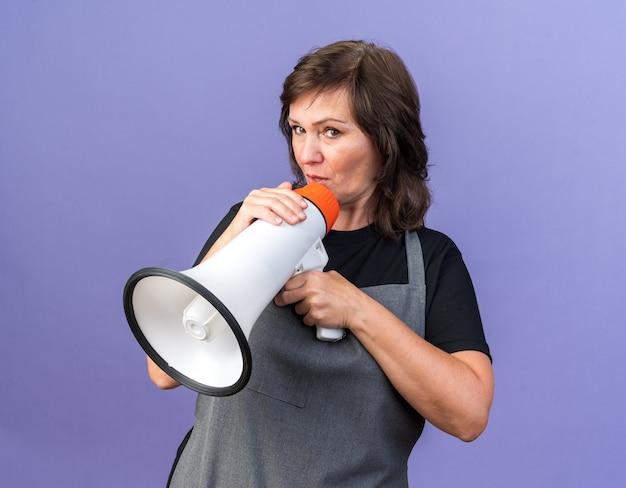 Onder de indruk volwassen blanke vrouwelijke kapper in uniform met luidspreker en kijken naar camera geïsoleerd op paarse achtergrond met kopie ruimte