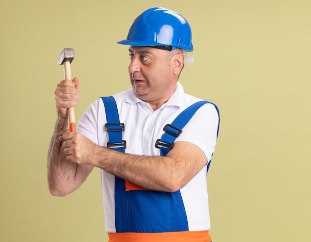 Onder de indruk volwassen bouwer man in uniform houdt en kijkt naar hamer geïsoleerd op olijfgroene muur
