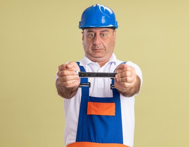 Onder de indruk volwassen bouwersman in uniform houdt en kijkt naar moersleutel op olijfgroen