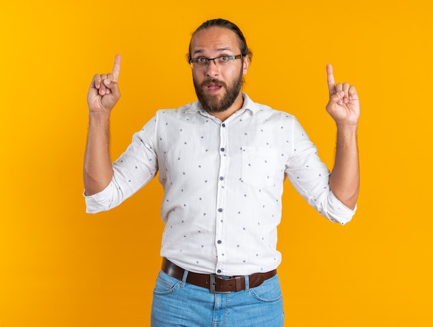 Onder de indruk volwassen knappe man met een bril die naar de camera kijkt en omhoog wijst, geïsoleerd op een oranje muur