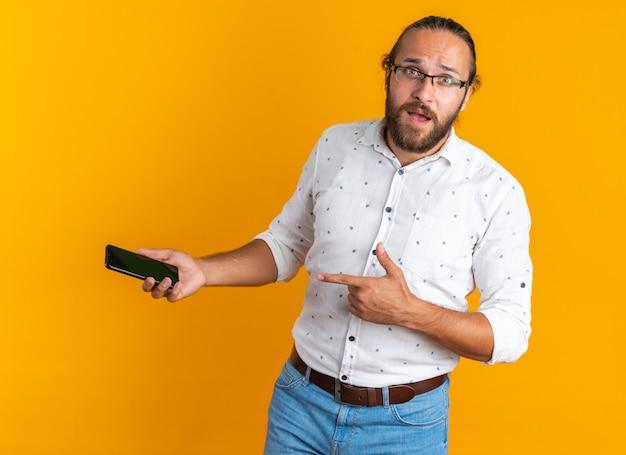 Onder de indruk volwassen knappe man met een bril die naar de camera kijkt en wijst naar een mobiele telefoon die op een oranje muur is geïsoleerd