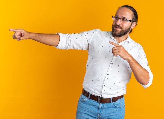 Onder de indruk volwassen knappe man met een bril die naar de zijkant kijkt en je gebaar doet geïsoleerd op een oranje muur