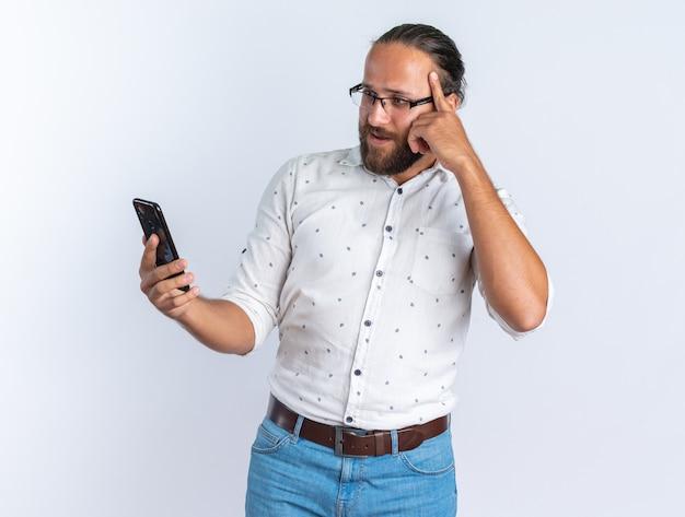 Onder de indruk volwassen knappe man met een bril die vasthoudt en naar een mobiele telefoon kijkt die een denkgebaar doet dat op een witte muur wordt geïsoleerd