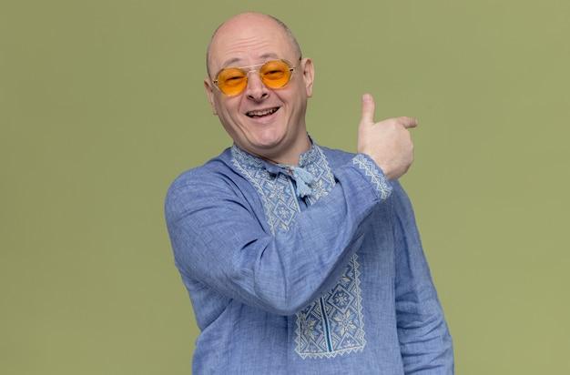 Onder de indruk volwassen man in blauw shirt met een zonnebril die naar achteren wijst