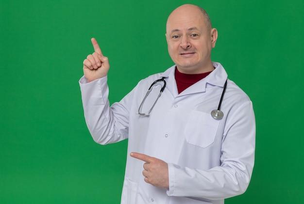 Onder de indruk volwassen man in doktersuniform met stethoscoop naar boven en aan de zijkant