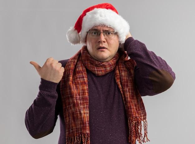 Onder de indruk volwassen man met een bril en een kerstmuts met sjaal om de nek die de hand op het hoofd houdt en naar de zijkant wijst geïsoleerd op een witte muur