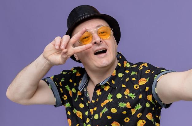 Onder de indruk volwassen man met zwarte hoge hoed die een zonnebril draagt die een overwinningsteken gebaart