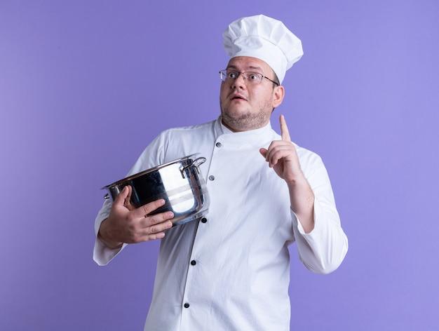 Onder de indruk volwassen mannelijke kok met een uniform van de chef-kok en een bril die een pot vasthoudt en naar de zijkant kijkt die omhoog wijst op een paarse muur