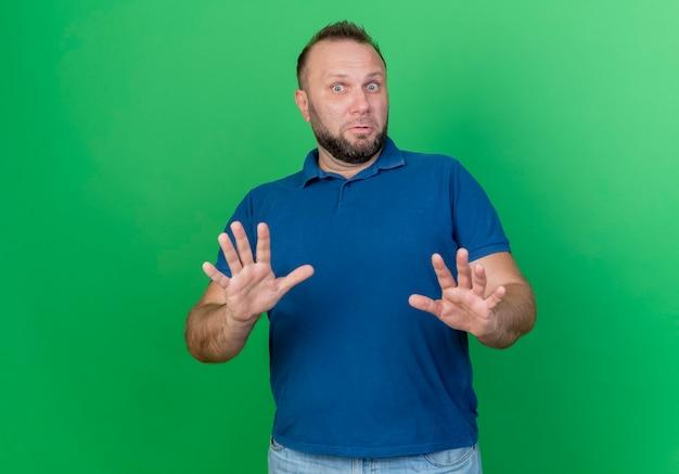 Onder de indruk volwassen slavische man die uit handen strekt die geen gebaar doen dat op groene muur met exemplaarruimte wordt geïsoleerd