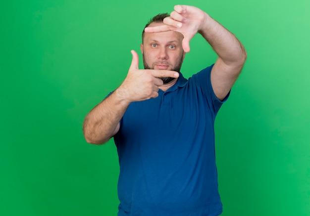 Onder de indruk volwassen slavische man en doet frame gebaar geïsoleerd op groene muur met kopie ruimte
