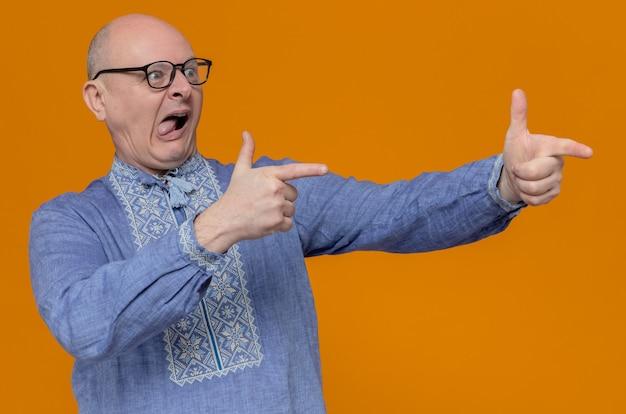 Onder de indruk volwassen slavische man in blauw shirt en met optische bril kijkend en wijzend naar de zijkant