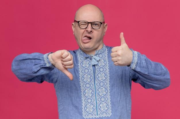 Onder de indruk volwassen slavische man in blauw shirt met bril steekt zijn tong uit, duimen omhoog en duimen omlaag