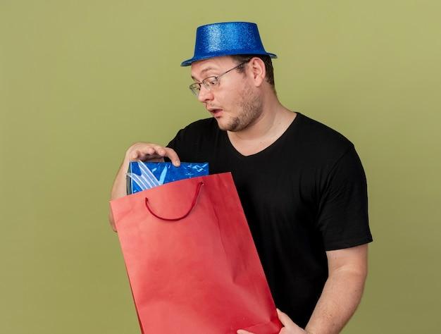 Onder de indruk volwassen slavische man in optische bril met blauwe feestmuts houdt en kijkt naar geschenkdoos in papieren boodschappentas