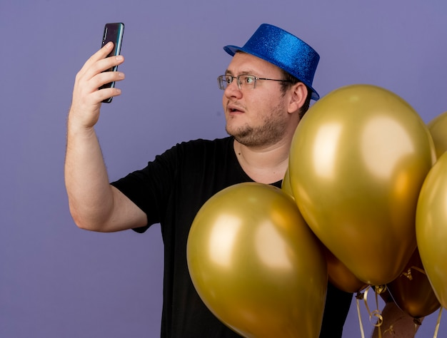 Onder de indruk volwassen slavische man in optische bril met blauwe feestmuts staat met heliumballonnen die naar de telefoon kijken