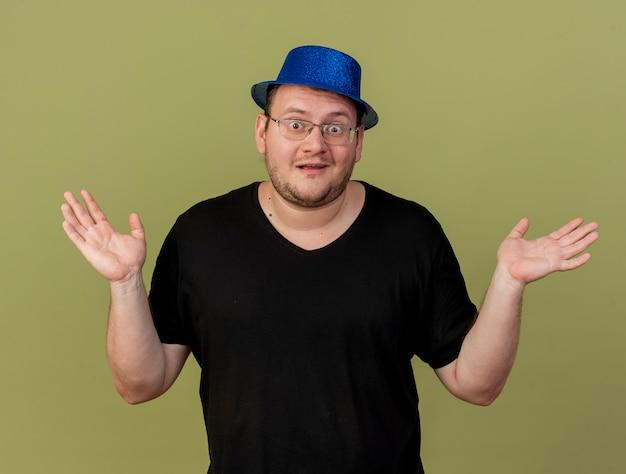 Onder de indruk volwassen slavische man in optische bril met blauwe feestmuts staat met opgeheven handen
