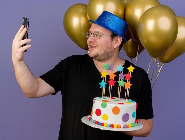 Onder de indruk volwassen slavische man in optische bril met blauwe feestmuts staat voor heliumballonnen houdt verjaardagstaart kijkend naar telefoon