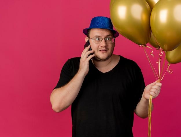 Onder de indruk volwassen slavische man met een optische bril met een blauwe feestmuts houdt vast en kijkt naar heliumballonnen die aan de telefoon praten