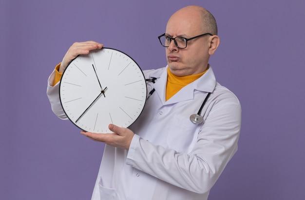Onder de indruk volwassen slavische man met optische bril in doktersuniform met een stethoscoop die de klok vasthoudt en bekijkt