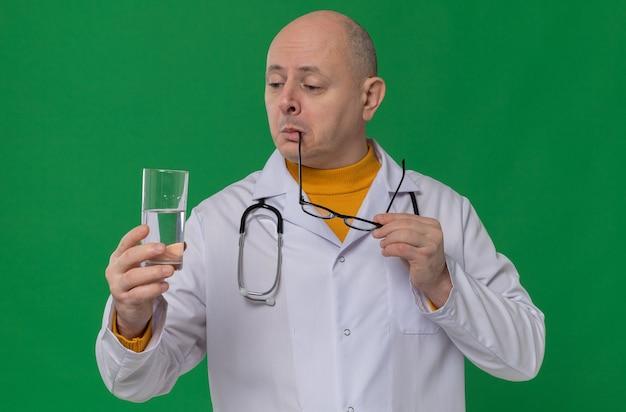 Onder de indruk volwassen slavische man met optische bril in doktersuniform met stethoscoop die glas water vasthoudt en kijkt