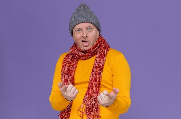 Onder de indruk volwassen slavische man met wintermuts en sjaal om zijn nek kijken en wijzend op de camera
