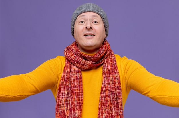 Onder de indruk volwassen slavische man met wintermuts en sjaal om zijn nek kijkend naar voren