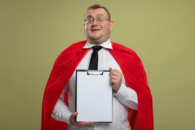 Onder de indruk volwassen slavische superheld man in rode cape bril en stropdas met klembord geïsoleerd op olijfgroene muur