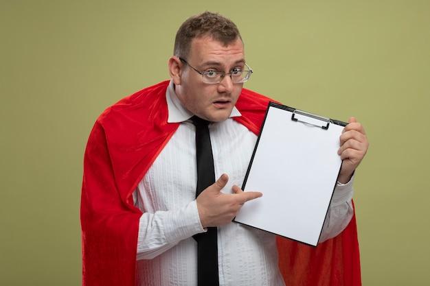 Onder de indruk volwassen slavische superheld man in rode cape bril en stropdas vasthouden en wijzend op klembord geïsoleerd op olijfgroene muur