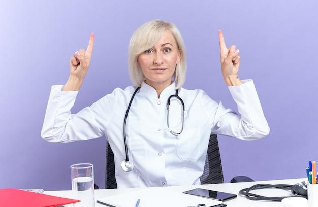 Onder de indruk volwassen slavische vrouwelijke arts in medische gewaad met stethoscoop zittend aan een bureau met office-hulpprogramma's omhoog geïsoleerd op paarse muur met kopieerruimte
