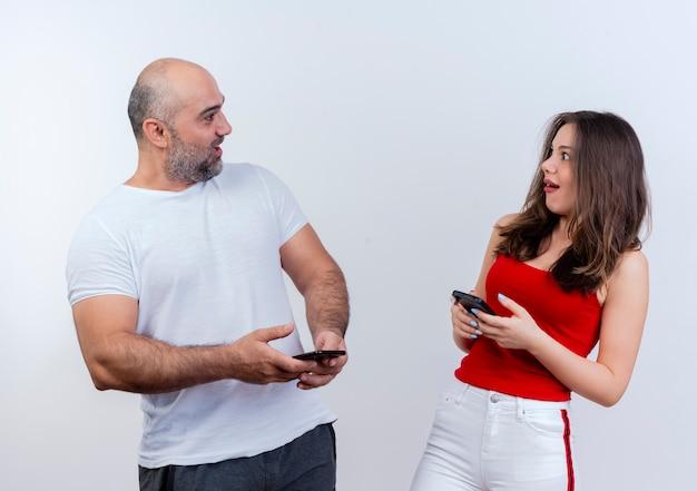 Onder de indruk volwassen stel dat allebei mobiele telefoons vasthoudt en naar elkaar kijkt