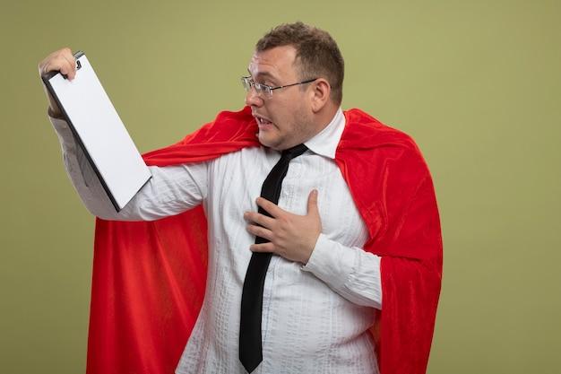 Onder de indruk volwassen superheld man in rode cape bril en stropdas vasthouden en kijken naar klembord hand op de borst zetten geïsoleerd op olijfgroene muur