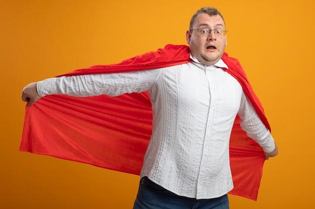 Onder de indruk volwassen superheld man in rode cape bril kijken voorkant grijpende cape doen alsof vliegen geïsoleerd op oranje muur