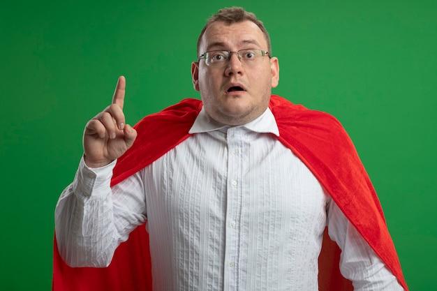 Onder de indruk volwassen superheld man in rode cape bril kijken voorzijde verhogen vinger geïsoleerd op groene muur