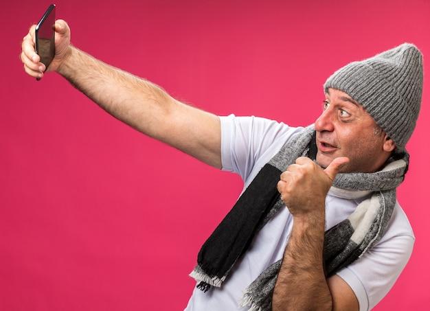 Onder de indruk volwassen zieke blanke man met sjaal om de nek dragen winter hoed duimen omhoog kijken naar telefoon nemen selfie geïsoleerd op roze muur met kopie ruimte