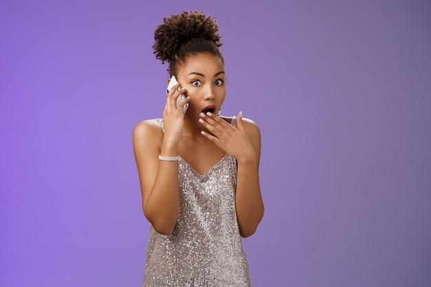 Onder de indruk vroeg zich af afro-amerikaanse vrouw laat haar kaak vallen naar adem happend dekken geopende mond roddelend hoor verbazingwekkende schokkende geruchten pratende smartphone kijkt sprakeloos bezorgde camera, blauwe achtergrond.