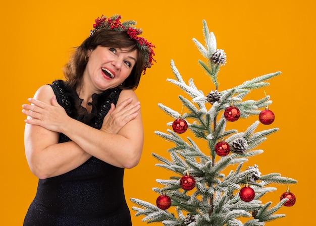 Onder de indruk vrouw van middelbare leeftijd dragen kerst hoofd krans en klatergoud slinger om nek staande in de buurt van versierde kerstboom houden handen gekruist op armen opzoeken geïsoleerd op oranje achtergrond