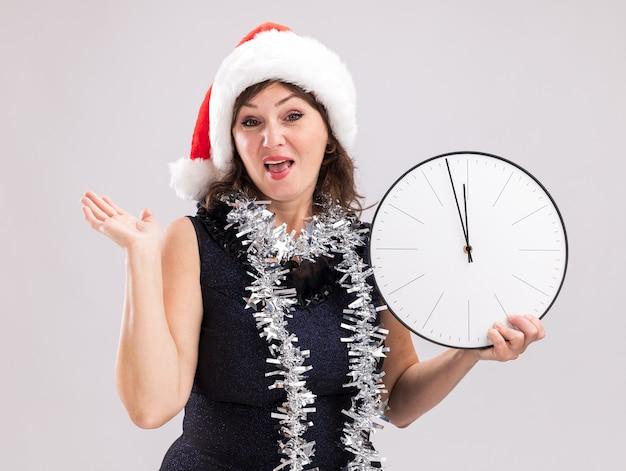 Onder de indruk vrouw van middelbare leeftijd dragen kerstmuts en klatergoud slinger rond nek bedrijf klok kijken camera weergegeven: lege hand geïsoleerd op witte achtergrond