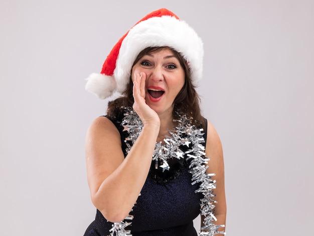Onder de indruk vrouw van middelbare leeftijd dragen kerstmuts en klatergoud slinger rond nek kijken camera fluisteren geïsoleerd op een witte achtergrond met kopie ruimte