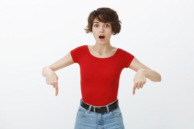 Onder de indruk vrouw zegt wauw en wijst met de vingers naar beneden bij de aankondiging