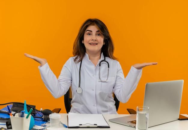 Onder de indruk vrouwelijke arts van middelbare leeftijd die medische mantel en stethoscoop draagt ?? die aan bureau zit met medische hulpmiddelenklembord en laptop die lege geïsoleerde handen toont