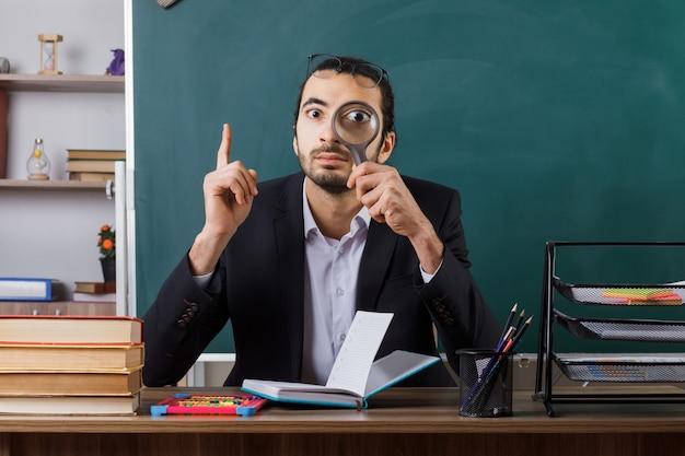 Onder de indruk wijst naar een mannelijke leraar die een bril draagt en kijkt met een vergrootglas aan tafel met schoolhulpmiddelen in de klas