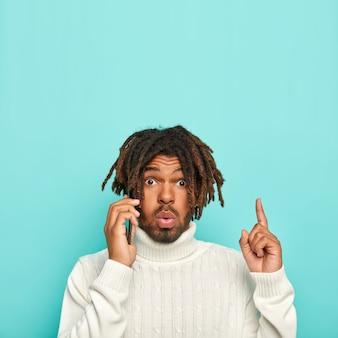 Onder de indruk zwarte man met dreadlocks heeft telefoongesprek, wijst naar boven met wijsvinger, draagt witte casual trui, geïsoleerd op blauwe achtergrond, kopieer ruimte voor uw tekst