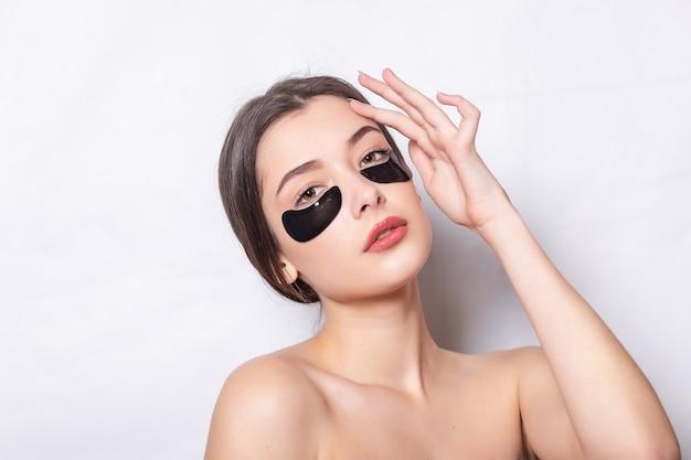 Onder de ooghuid zwarte vlek. close-up van mooie jonge vrouw gezicht met hydraterende collageen masker pad op gezonde frisse gezichtshuid op witte achtergrond