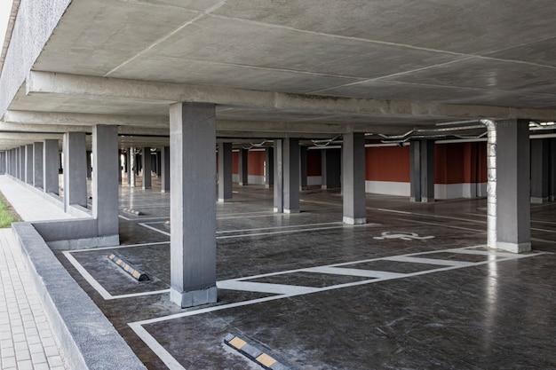 Onder het woongebouw bevindt zich een ondergrondse parkeergarage. een plek voor het parkeren en opslaan van persoonlijke voertuigen van bewoners van een gebouw met meerdere verdiepingen.