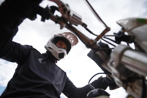 Onder weergave van geconcentreerde man in de hendel van de helmholding terwijl hij klaar is voor motorrace