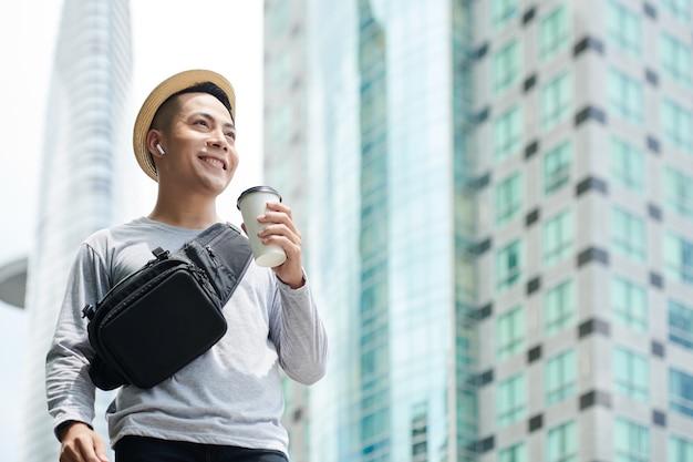 Onder weergave van lachende jonge vietnamese man met heuptas die naar muziek luistert in draadloze oordopjes en koffiekopje vasthoudt terwijl hij langs straat met wolkenkrabbers loopt