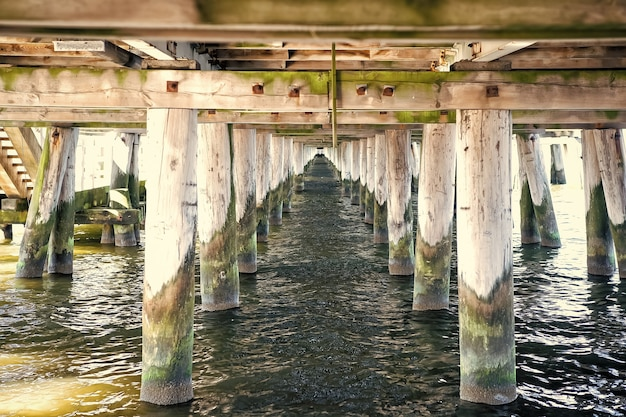 Onder zicht op houten constructie van houten brug met water buiten als natuurlijke achtergrond