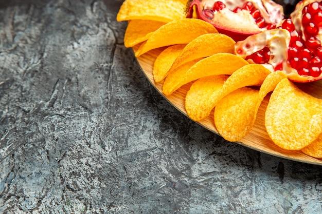Onderaanzicht aardappelkarbonades granaatappel op ovale serveerplank op donkere achtergrond